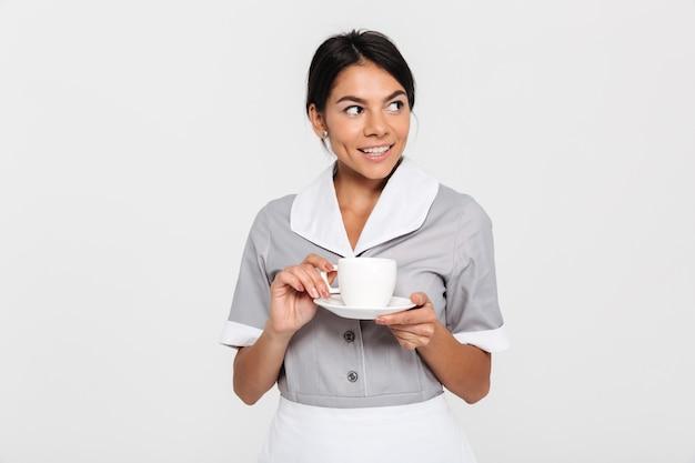 Retrato de mulher jovem morena feliz em uniforme cinza, segurando a xícara de chá e olhando de lado