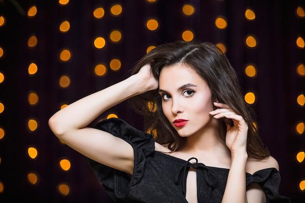 Retrato de mulher jovem morena linda e luxuosa em fundo de luzes douradas.