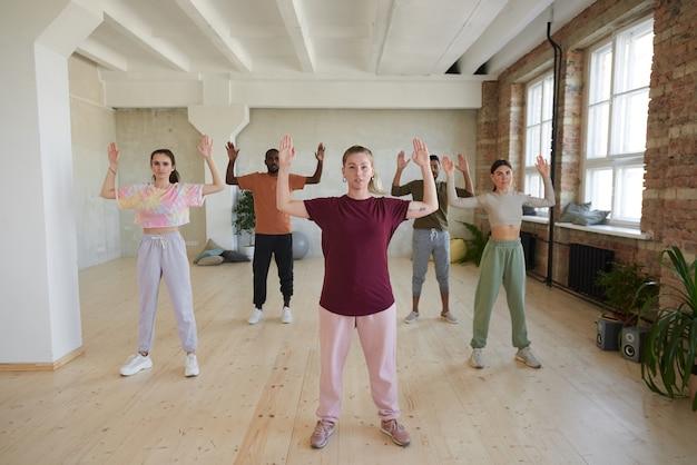 Retrato de mulher jovem mostrando exercícios e pessoas repetindo para ela durante a ginástica