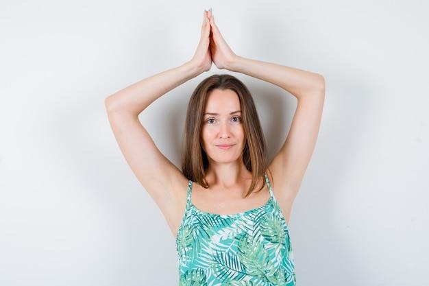 Retrato de mulher jovem mostrando gesto de namastê acima da cabeça e olhando esperançoso de frente