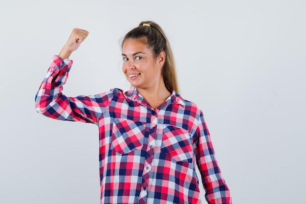 Retrato de mulher jovem mostrando os músculos do braço em uma camisa casual e olhando orgulhosa de frente