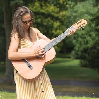 Retrato, de, mulher jovem, música jogando, ligado, guitarra, parque