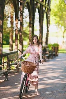 Retrato de mulher jovem na moda em vestido floral rosa longo parar de andar em bicicleta vintage com cesta para compras, comida ou flores ao ar livre, tempo de recreação feminino lindo na primavera ou parque de verão.