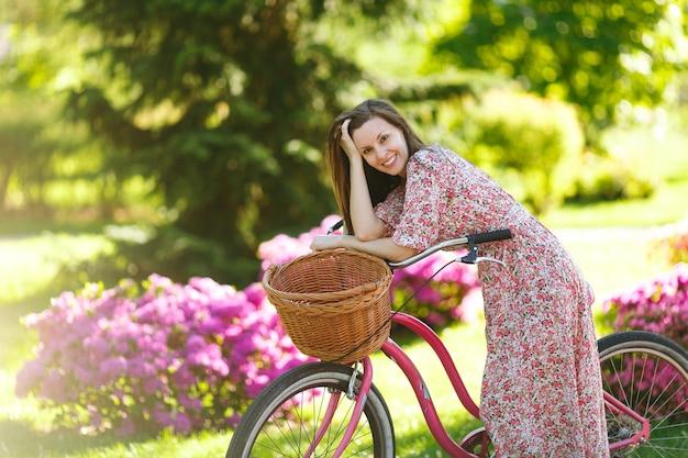 Retrato de mulher jovem na moda em vestido floral rosa longo parar de andar em bicicleta vintage com cesta para compras em fundo de flores ao ar livre. tempo de recreação muito feminino no parque de primavera ou verão