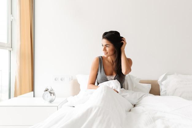 Retrato de mulher jovem relaxada, descansando na cama depois de dormir com roupa limpa branca no quarto e olhando pela janela