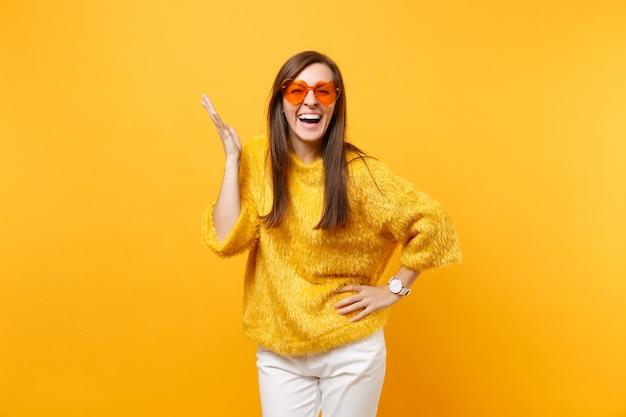 Retrato de mulher jovem rindo com suéter de pele, calça branca, óculos coração laranja, espalhando as mãos isoladas em fundo amarelo brilhante. emoções sinceras de pessoas, conceito de estilo de vida. área de publicidade.