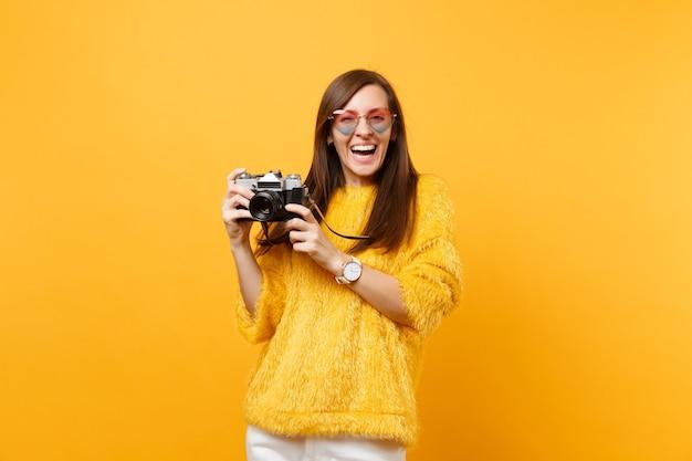 Retrato de mulher jovem rindo em óculos de coração, tirando fotos na câmera fotográfica vintage retrô isolada em fundo amarelo brilhante. emoções sinceras de pessoas, conceito de estilo de vida. área de publicidade.