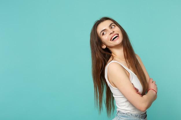 Retrato de mulher jovem rindo em roupas leves casuais, olhando de lado, de mãos dadas cruzadas isoladas no fundo da parede azul turquesa. conceito de estilo de vida de emoções sinceras de pessoas. simule o espaço da cópia.