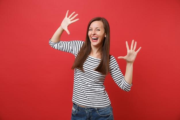 Retrato de mulher jovem rindo em roupas listradas casuais em pé e espalhando as mãos e os dedos