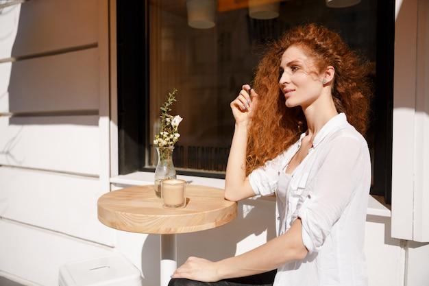 Retrato de mulher jovem ruiva bonita sentada em um café