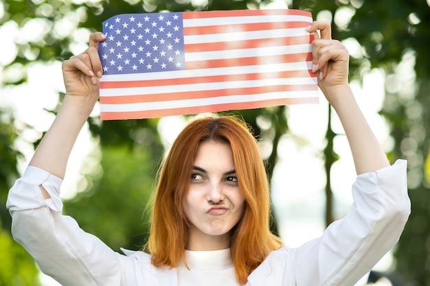 Retrato de mulher jovem ruiva engraçada segurando a bandeira nacional dos eua nas mãos em pé ao ar livre no parque de verão. menina positiva comemorando o dia da independência dos estados unidos.