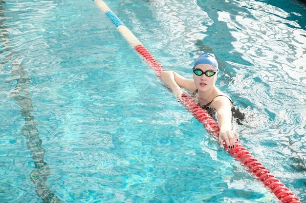 Retrato de mulher jovem saudável com óculos e boné pendurado no divisor de pista da piscina