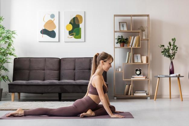 Retrato de mulher jovem se alongando em casa no tapete