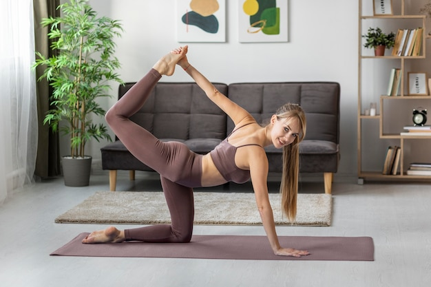 Retrato de mulher jovem se exercitando em casa no tapete