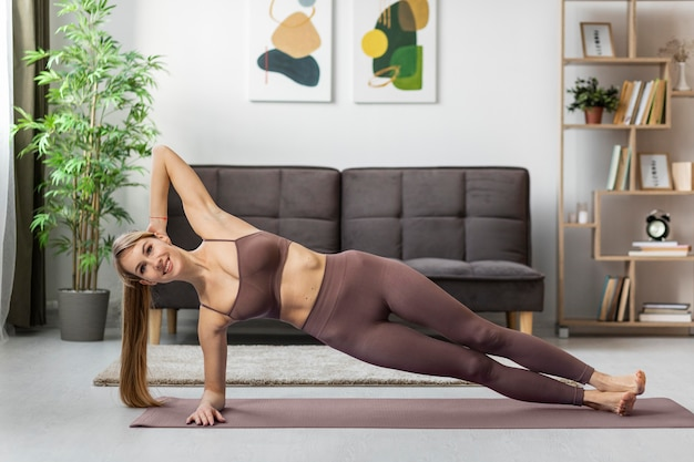 Retrato de mulher jovem se exercitando em casa