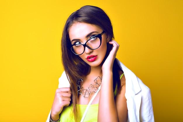 Retrato de mulher jovem sensual, cabelos longos e morenos, óculos retrô, look casual brilhante de negócios