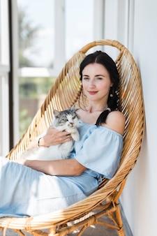 Retrato, de, mulher jovem, sentando, com, dela, gato, ligado, cadeira