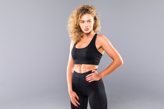 Retrato de mulher jovem sexy com as mãos nos quadris. fitness feminino com corpo musculoso pronto usando luvas de mão para treino na parede cinza