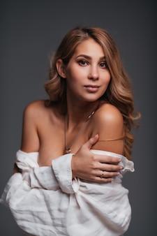 Retrato de mulher jovem sexy posando de camisa branca