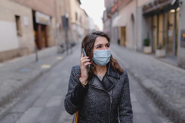 Retrato de mulher jovem sorridente caucasiano de close-up andando no centro de uma cidade durante o inverno frio e falando tendo um telefonema.
