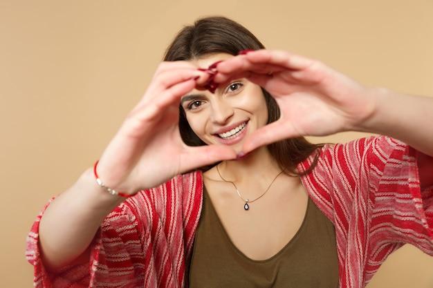 Retrato de mulher jovem sorridente com roupas casuais, mostrando forma de coração com as mãos isoladas no fundo da parede bege pastel no estúdio. emoções sinceras de pessoas, conceito de estilo de vida. simule o espaço da cópia.