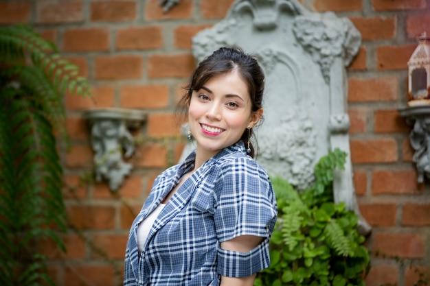 Retrato de mulher jovem sorridente contra jardim