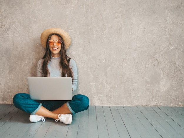 Retrato de mulher jovem sorridente criativa em óculos de sol. linda garota sentada no chão perto da parede cinza.