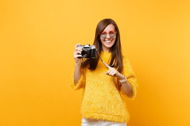 Retrato de mulher jovem sorridente em copos de coração apontando o dedo indicador na câmera fotográfica vintage retrô isolada em fundo amarelo brilhante. emoções sinceras de pessoas, conceito de estilo de vida. área de publicidade.