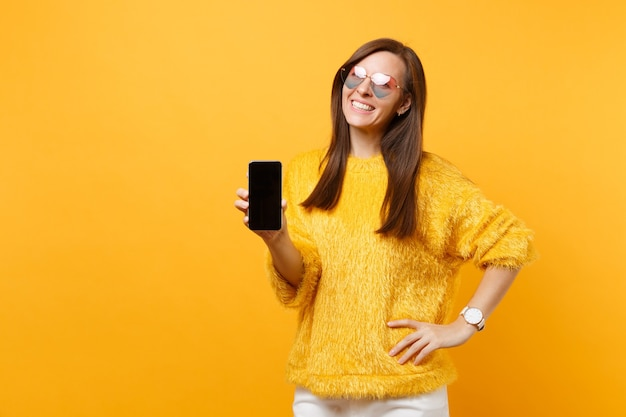 Retrato de mulher jovem sorridente em copos de coração, segurando o telefone móvel com tela vazia preta em branco, isolada em fundo amarelo brilhante. emoções sinceras de pessoas, conceito de estilo de vida. área de publicidade.