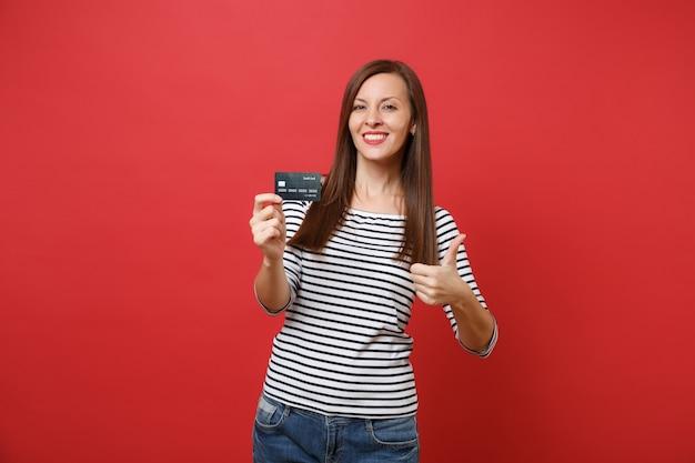 Retrato de mulher jovem sorridente em roupas listradas casuais, aparecendo o polegar, segurando o cartão de crédito isolado no fundo da parede vermelha brilhante. emoções sinceras de pessoas, conceito de estilo de vida. simule o espaço da cópia.