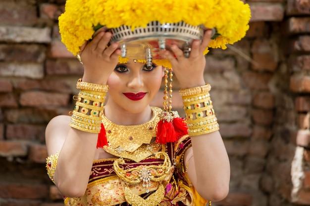 Retrato de mulher jovem sorridente em roupas tradicionais de bali, segurando o buquê de flores no templo