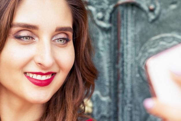 Retrato de mulher jovem sorridente está tomando selfie por smartphone ao ar livre.