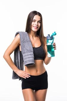 Retrato de mulher jovem sorridente feliz no desgaste de fitness com garrafa de água, isolada no branco