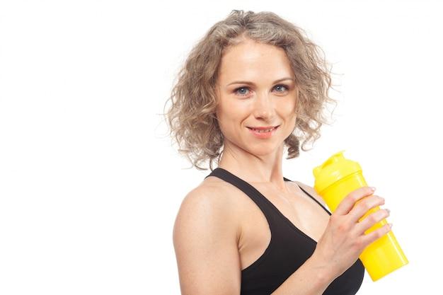 Retrato de mulher jovem sorridente feliz no desgaste de fitness com garrafa de água