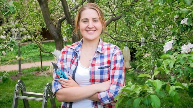 Retrato de mulher jovem sorridente feliz posando em pomar de jardim florescendo.