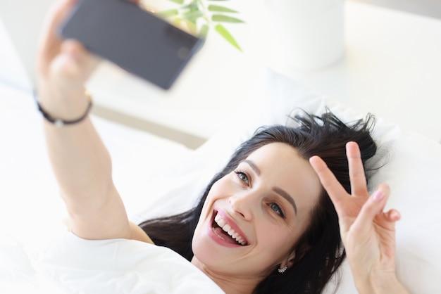Retrato de mulher jovem sorridente na cama branca tirando selfie no smartphone