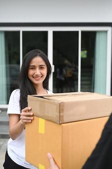 Retrato de mulher jovem sorridente, recebendo a caixa do pacote do entregador em casa.