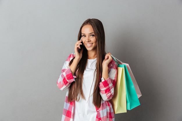 Retrato de mulher jovem sorridente segurando sacolas de compras, falando no celular