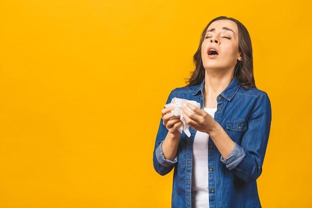 Retrato de mulher jovem tossindo com um guardanapo, resfriado, sentindo-se doente