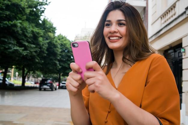Retrato de mulher jovem usando seu telefone celular enquanto caminha ao ar livre na rua