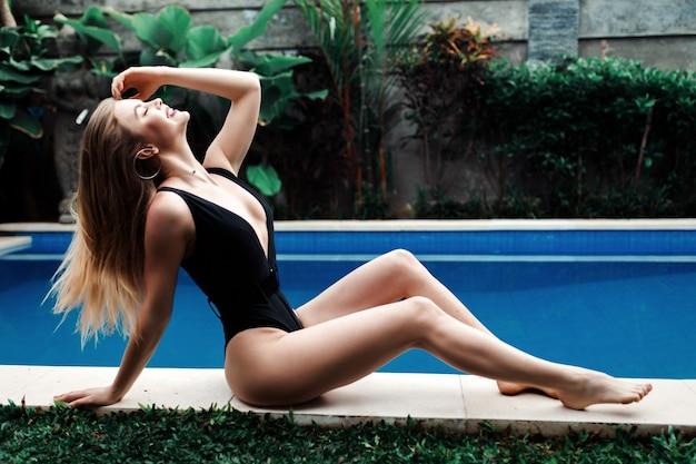 Retrato de mulher jovem vestida de preto em pele de porco à beira da piscina infinita