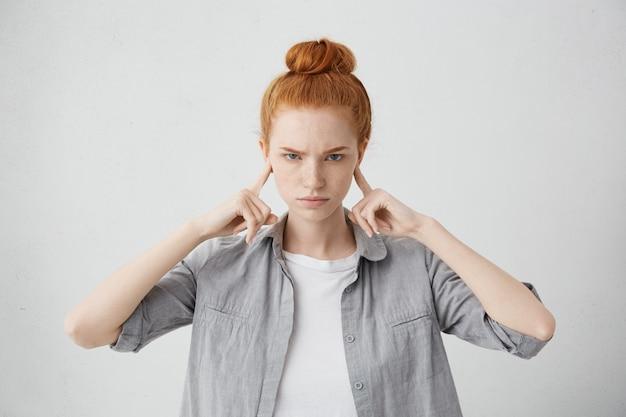 Retrato de mulher jovem zangada e irritada, carrancuda e tapando os ouvidos com os dedos não suporta barulho alto ou ignora situação desagradável estressante ou conflito. emoções negativas humanas