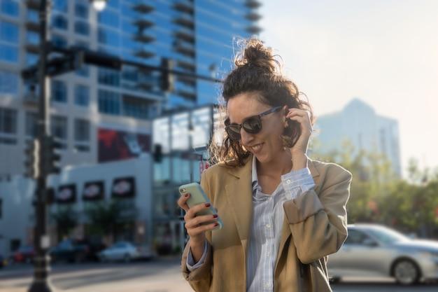 Retrato de mulher latina com óculos de sol sorrindo enquanto olha para o celular, cidade em segundo plano, foco seletivo e espaço de cópia