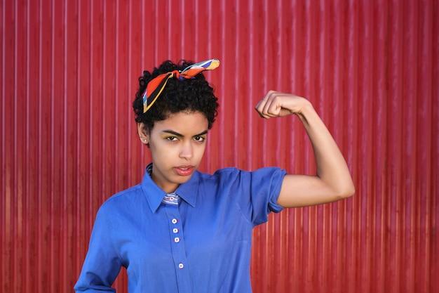 Retrato de mulher latina séria na parede vermelha, olhando para a frente, mostrando seu bíceps.