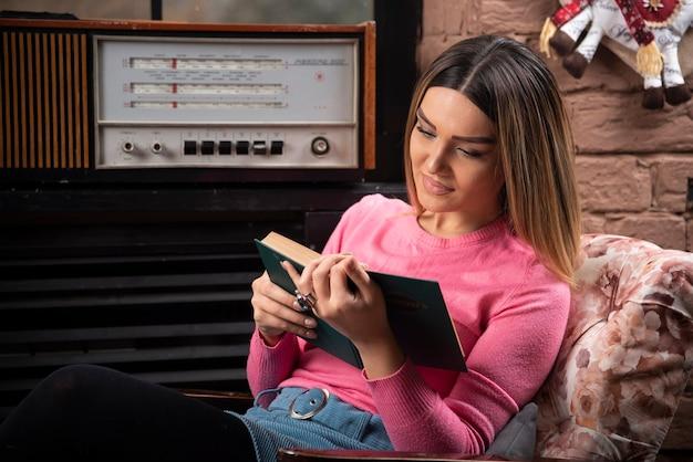 Retrato de mulher lendo livro em casa