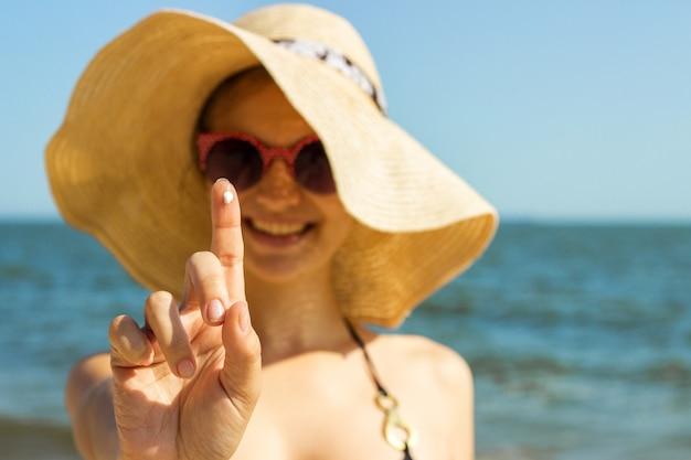 Retrato, de, mulher, levando, skincare, com, protetor solar, loção, em, praia