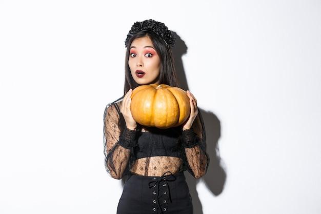 Retrato de mulher levantando uma abóbora pesada, preparando-se para o dia das bruxas