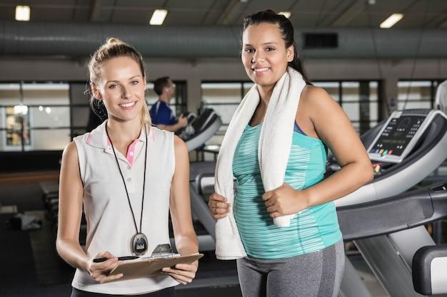Retrato, de, mulher, ligado, treadmill, e, treinador, em, ginásio