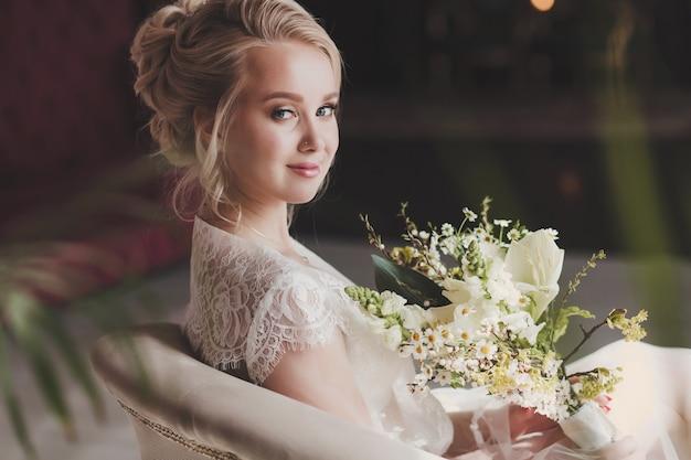 Retrato de mulher linda noiva com vestido de renda, sentada na cadeira