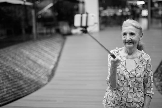 Retrato de mulher linda turista sênior relaxando ao redor da cidade de bangkok em preto e branco